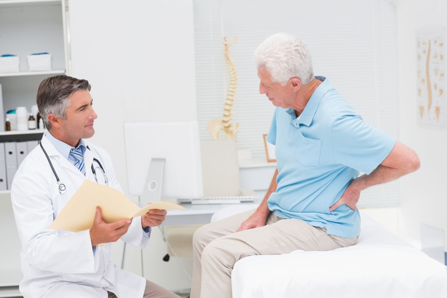 Male doctor discussing reports with senior patient suffering fro